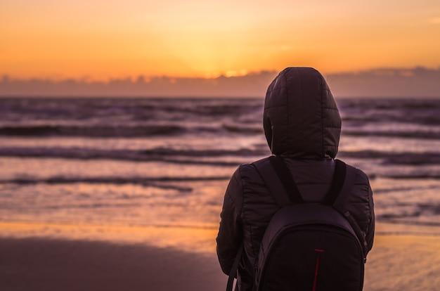 Mulher olhando para a praia do horizonte