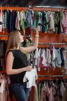 Mulher olhando para a roupa do bebê