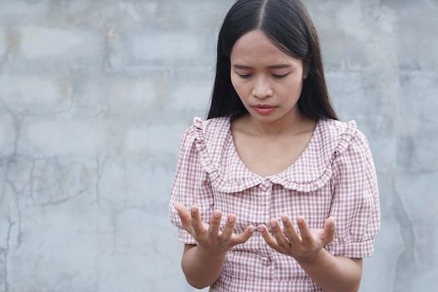 Mulher olhando para as mãos dela