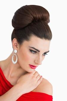 Mulher olhando para baixo ao usar um vestido vermelho