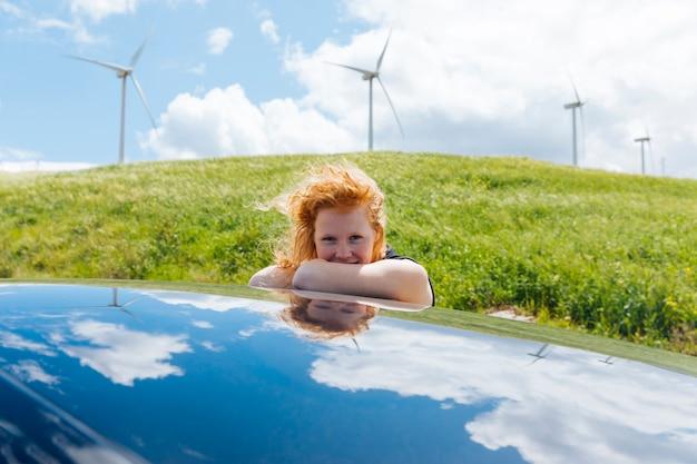 Mulher olhando para câmera saindo da janela do carro e colocando as mãos no telhado