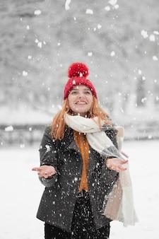 Mulher olhando para cima e de pé na neve