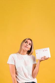 Mulher olhando para cima e segurando o calendário de menstruação