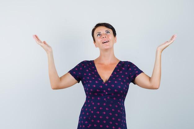Mulher olhando para cima, levantando os braços no vestido e parecendo grata. vista frontal.