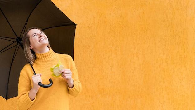 Mulher olhando para cima, segurando um guarda-chuva com espaço de cópia