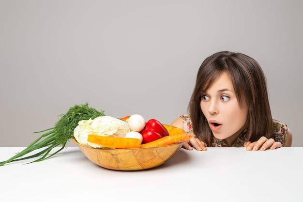 Mulher olhando para comida vegana verde. emoção surpresa.