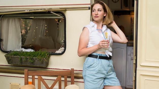 Mulher olhando para longe ao lado de seu trailer