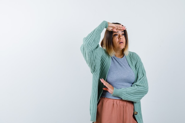 Mulher olhando para longe com a mão na cabeça em roupas casuais e olhando espantada, vista frontal.