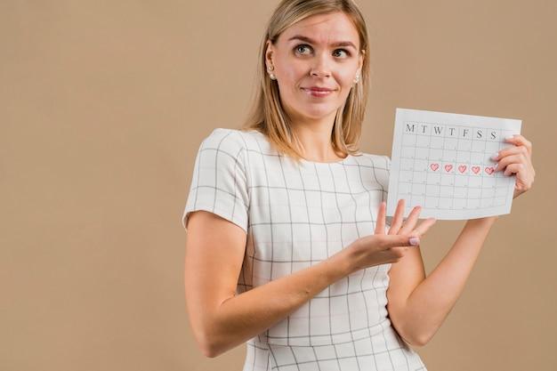 Mulher olhando para longe e mostrando seu calendário menstrual