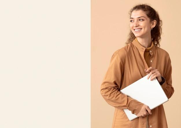 Mulher olhando para longe e segurando um espaço de cópia do laptop