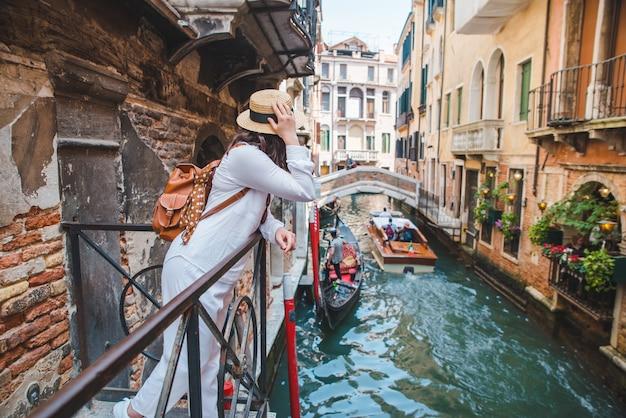 Mulher olhando para o canal com gandola, férias de verão