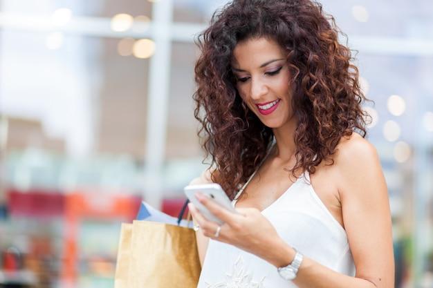 Mulher olhando para o celular enquanto caminhava na rua