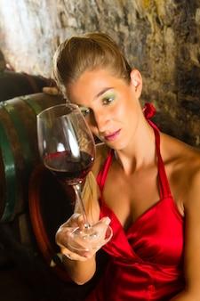 Mulher olhando para o copo de vinho na adega