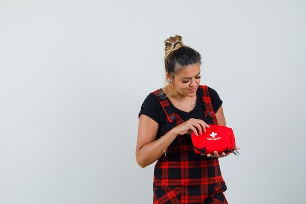 Mulher olhando para o kit de primeiros socorros com vestido avental e curiosa, vista frontal.