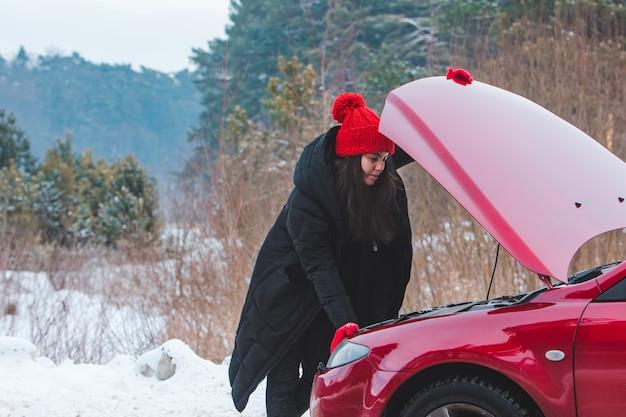 Mulher olhando para o motor do carro quebrado no espaço da cópia do lado da estrada de inverno