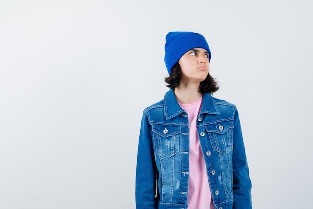 Mulher olhando para o outro lado com camiseta, jaqueta jeans e gorro parecendo pensativa