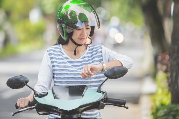 Mulher olhando para o relógio enquanto andava de moto no stree