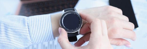 Mulher olhando para o relógio inteligente no conceito de prazo de close no local de trabalho