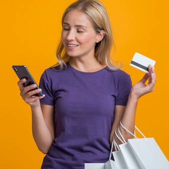 Mulher olhando para o smartphone, segurando um cartão de crédito e sacolas de compras