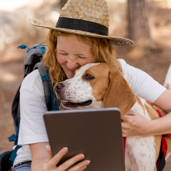 Mulher olhando para o tablet e abraçando o cachorro