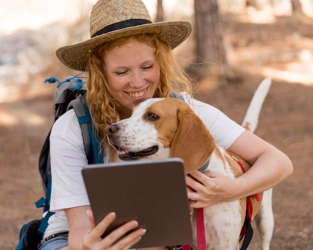 Mulher olhando para o tablet e segurando o cachorro