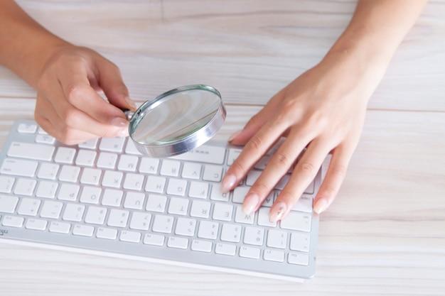 Mulher olhando para o teclado com uma lupa