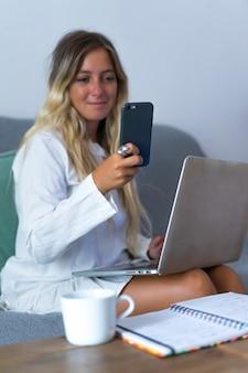 Mulher olhando para o telefone durante o teletrabalho