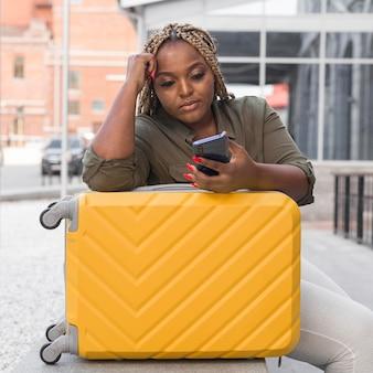 Mulher olhando para o telefone enquanto espera por uma ligação
