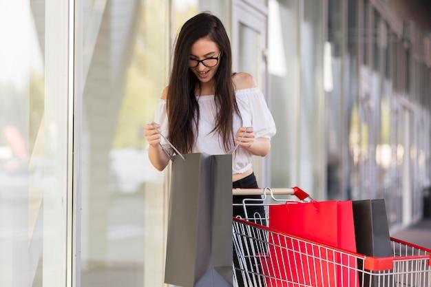 Mulher olhando para sacolas de compras