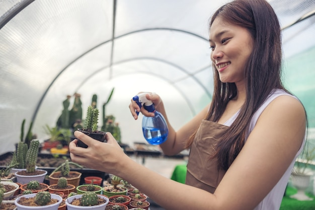 Mulher olhando para um cacto no centro do jardim com efeito de estufa, jovem asiática olhando para um pequeno cacto