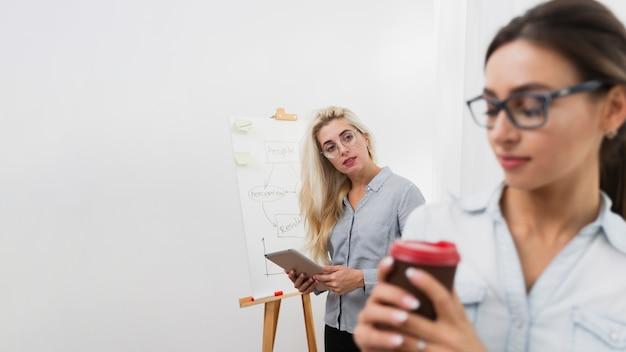 Mulher olhando para um colega segurando um café