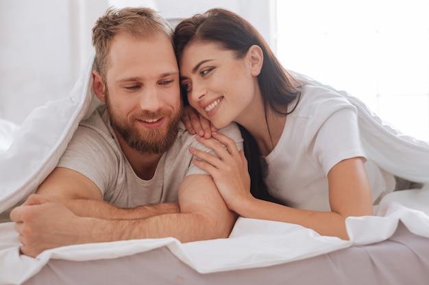 Mulher olhando para um homem com os olhos cheios de amor enquanto os dois estão deitados na cama cobertos por um edredom