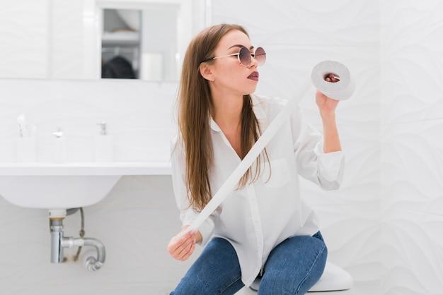 Mulher olhando para um papel higiênico