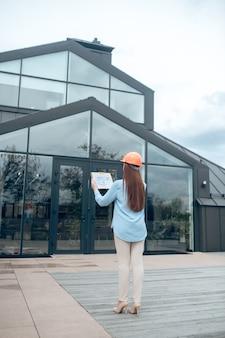 Mulher olhando para um prédio de costas para a câmera
