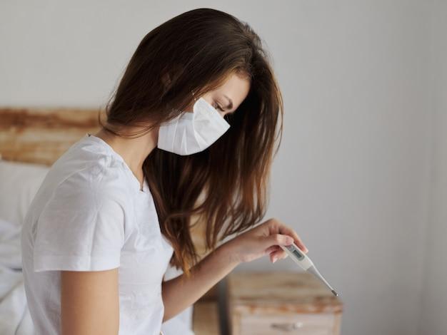Mulher olhando para um termômetro verificando a temperatura no quarto
