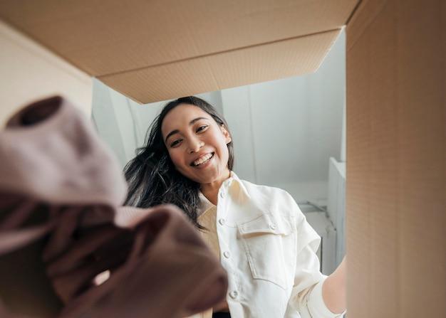 Mulher olhando para uma caixa com roupas