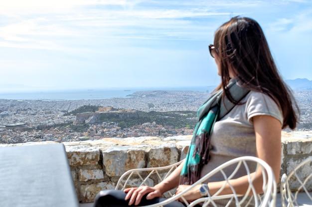 Mulher olhando para uma grande cidade de atenas e a colina da acrópole