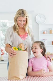 Mulher olhando para uma mercearia ao lado de uma filha sorridente