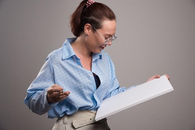 Mulher olhando para uma tela vazia e escova no fundo cinza