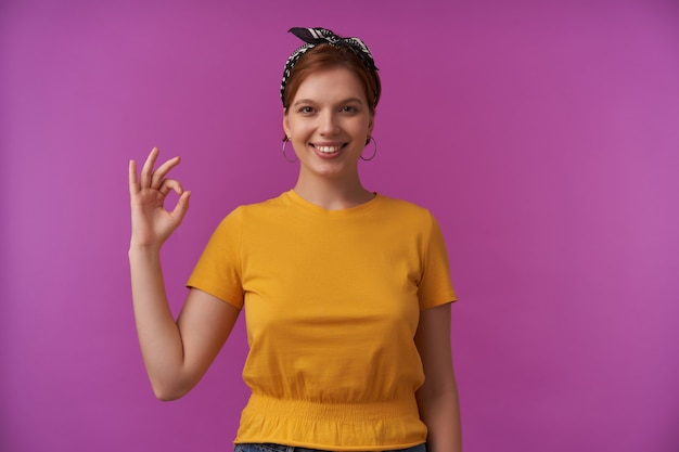 Mulher olhando para você vestindo camiseta amarela elegante de verão e bandana preta emoção feliz feliz ok dedos posando isolados no roxo