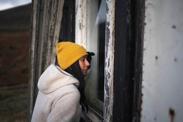 Mulher olhando pela janela de uma cabine com estrutura em a