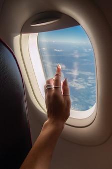 Mulher olhando pela janela do avião durante o nascer do sol