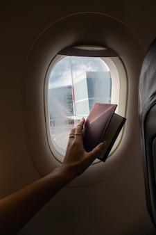 Mulher olhando pela janela do avião e mostrando o passaporte