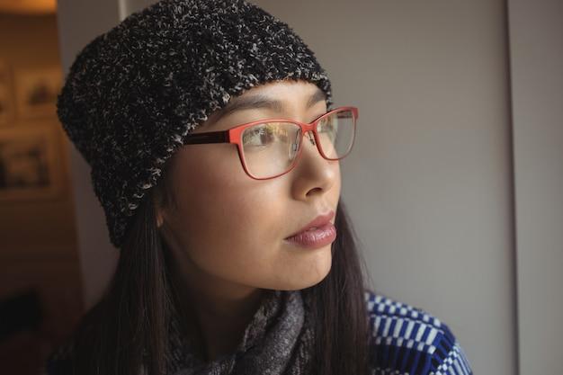 Mulher olhando pela janela em um café