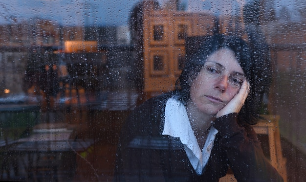 Mulher olhando pela janela em um dia chuvoso