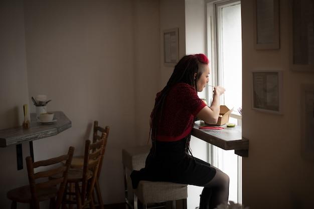 Mulher olhando pela janela enquanto come uma salada
