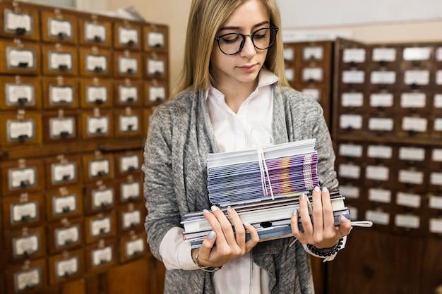 Mulher olhando pilha de livros e cadernos