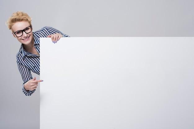 Mulher olhando por trás do cartaz