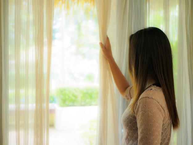 Mulher olhando por uma janela para o conceito solitário e triste