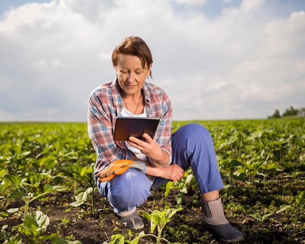 Mulher olhando seu tablet enquanto cultivava